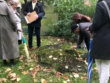 Die umgebettete Grabstätte der Kameliter und die bemooste Grabplatte davor.